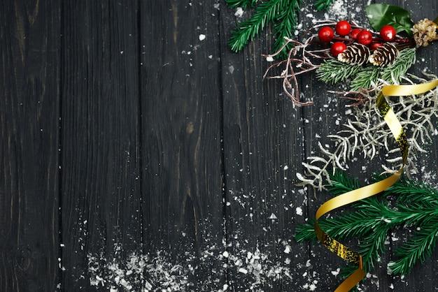 Banner mit serpntinweißer baumdekoration für die feiertage weihnachten und neujahr im winter mit schnee auf einem hölzernen hintergrund
