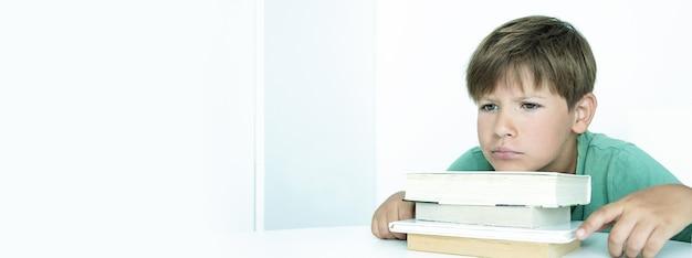 Banner. trauriger junge mit buch macht schulhausaufgaben. zurück zur schule. unglücklicher schüler mit lehrbüchern. fernunterricht