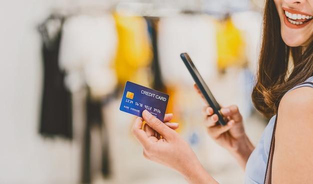 Banner und webseite oder cover-vorlage einer asiatischen frau, die kreditkarte mit handy verwendet