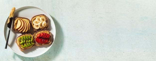Banner verschiedener sandwiches mit erdnussbutter und erdbeeren, sellerie, banane und apfel auf einem teller auf dem tisch. perfektes frühstück am morgen