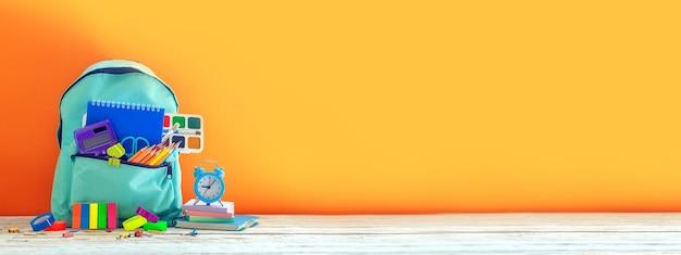 Banner voller türkisfarbener schulrucksack mit briefpapier auf tisch auf orange back to school-konzept