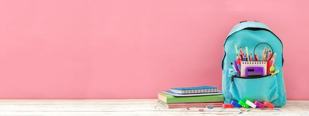Banner voller türkisfarbener schulrucksack mit briefpapier auf tisch auf rosa back to school-konzept