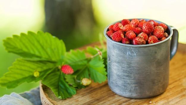 Banner walderdbeeren in einem metallbecher auf holztablett