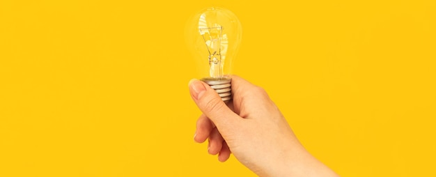 Bannerideenkonzept, frauenhand mit glühbirne auf orangefarbenem und gelbem hintergrund, isoliert und kopienraumfoto