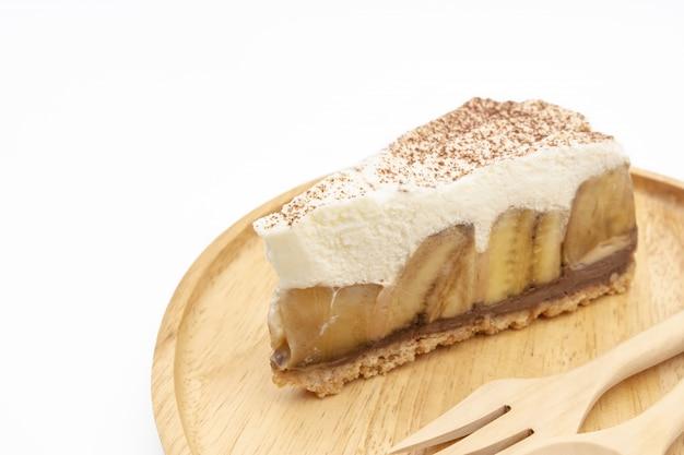 Banoffee-torte, schlagsahne und banane auf dem weißen hintergrund des hölzernen plattenisolats