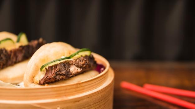 Bao brötchen gedämpftes sandwich im korbdampfer mit essstäbchen auf holztisch