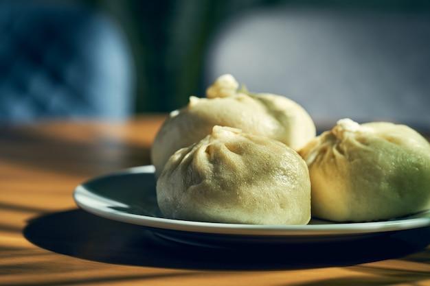 Baozi mit verschiedenen füllungen (rind- oder schweinefleisch) in einem weißen teller. chinesisches rezept und küche. chinesisches gedämpftes fleischbrötchen
