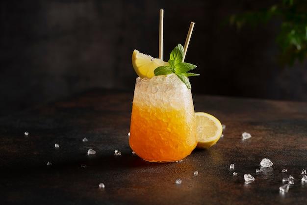 Bar-konzept, cocktail mit crushed ice, zitrone und minze auf dem rindenhintergrund,