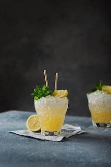 Bar-konzept: gelber cocktail mit zitrone, minze und crushed ice an der schwarzen wand, selektives fokusbild