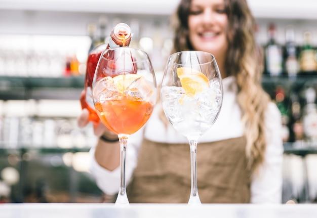 Bar lady bereitet cocktails zu und gießt alkohol in die gläser