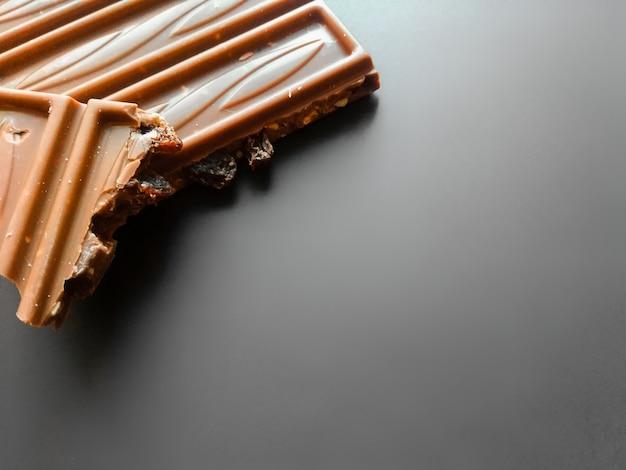 Bar milchschokolade mit den zerquetschten haselnuss- und alkoholrosinen lokalisiert