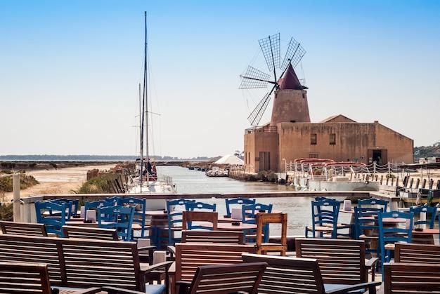 Bar mit blick auf mozia-salinen und eine alte windmühle in marsala, sizilien