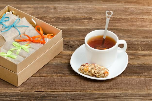 Bar müsli, eine tasse tee und kisten mit riegeln. gesundes frühstück