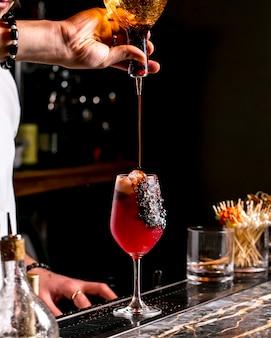 Bar tender gießt sirup in rotes cocktailglas