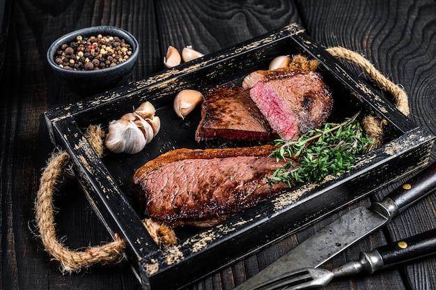 Barbecue gegrillte rump cap oder brasilianisches picanha-rindfleischsteak in einem holztablett. schwarzer hölzerner hintergrund. ansicht von oben.