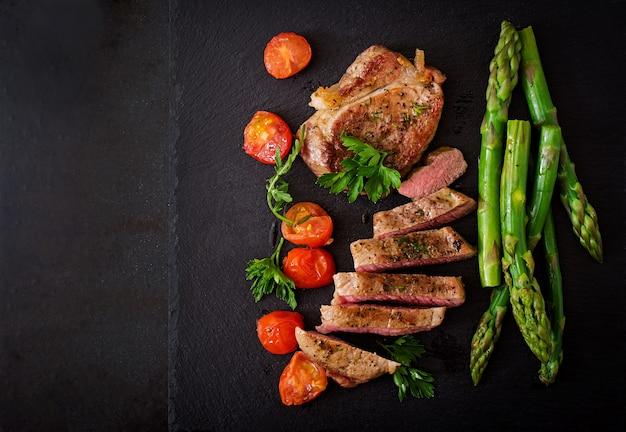 Barbecue gegrilltes rindersteakfleisch mit spargel und tomaten.