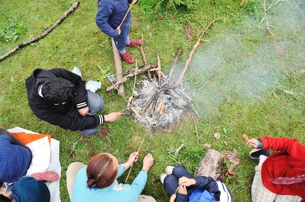 Barbecue in der natur, gruppe von personen, die würste auf feuer vorbereiten
