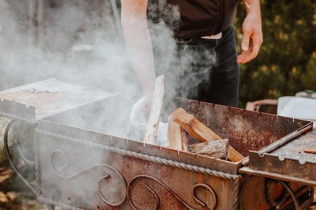 Barbecue mit brennholz, flamme und rauch auf dem hinterhof. picknick-konzept. der fokus liegt auf wald.