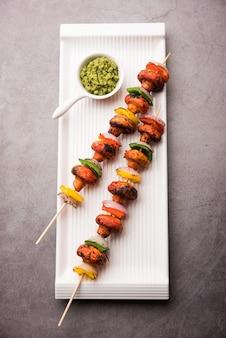 Barbecue oder tandoori pilz tikka, serviert in einem teller mit grünem chutney und ketchup. selektiver fokus