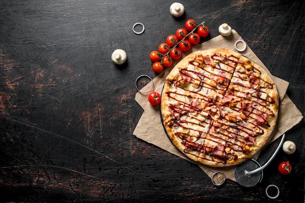 Barbecue-pizza auf papier mit kirschtomaten auf dunklem rustikalem tisch