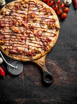 Barbecue-pizza mit huhn, speck und sojasauce auf dunklem rustikalem tisch