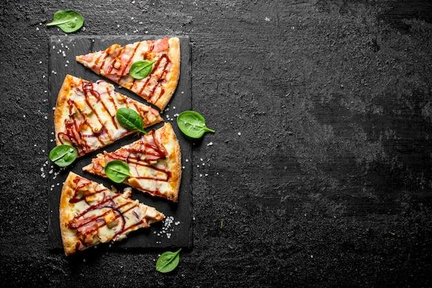 Barbecue-pizzastücke mit speck, huhn und käse auf schwarzem rustikalem tisch.