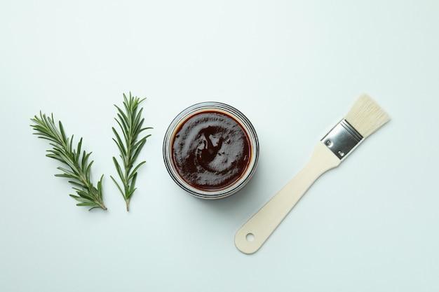 Barbecue-sauce, rosmarin und pinsel auf weißem hintergrund