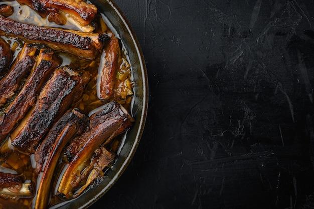 Barbecue schweinefleisch spareribs set, in bratpfanne aus gusseisen, auf schwarzem steintisch, draufsicht flach legen