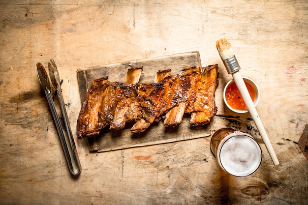 Barbecue-schweinerippchen mit tomatensauce und bier auf hölzernem hintergrund Premium Fotos