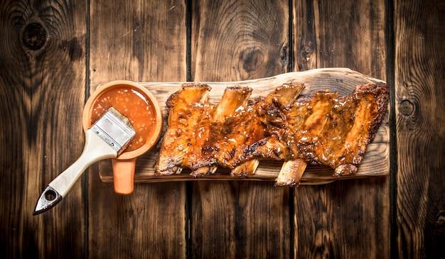 Barbecue schweinerippchen mit würziger sauce auf einem holztisch