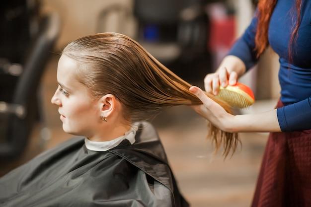 Barber girl kämmen nasse haare im friseursalon