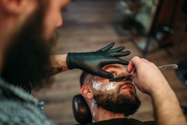 Barber rasiert den bart des kunden mit einem rasiermesser im friseursalon.