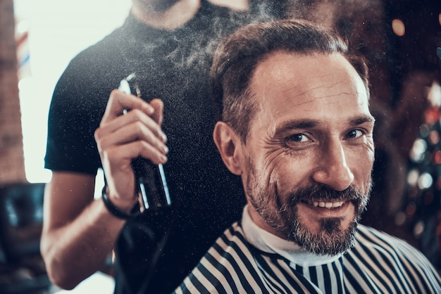 Barber shaves handsome smiling man mit rasiermesser.