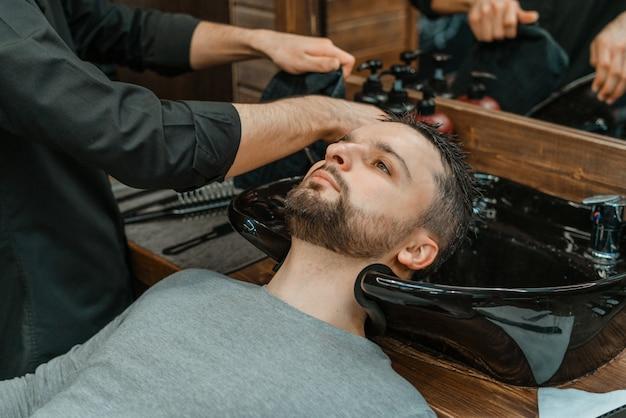 Barbershop, ein mann wird seine haare gewaschen. barber wäscht seinen klienten. haare und bärte nach dem schneiden waschen. körperpflege