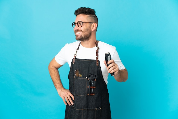 Barbier-mann in einer schürze posiert mit armen an der hüfte und lächelt