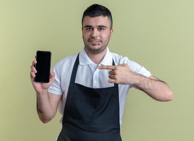 Barbier-mann in schürze, der smartphone zeigt, der mit dem zeigefinger darauf zeigt und selbstbewusst lächelt
