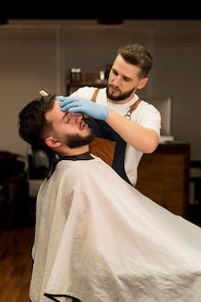 Barbier rasieren und konturieren den bart eines männlichen kunden