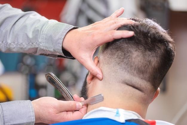 Barbierhände schließen oben und rasieren kopf eines bärtigen mannes.