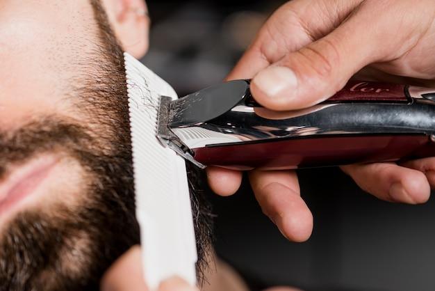Barbiers hand, die den bart des mannes mit elektrischem trimmer kennzeichnet