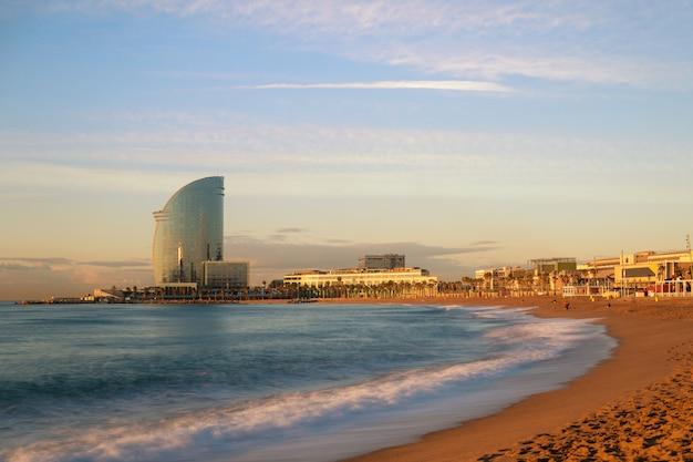 Barceloneta beach in barcelona mit buntem himmel bei sonnenaufgang in spanien. vorort von barcelona,