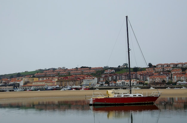 Barco en la mar junta a casas con reflejo Premium Fotos