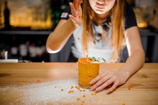Bardame dekoriert alkoholischen cocktail mit minze und getrockneter orange, indem sie einen bitter sanddorn hinzufügt