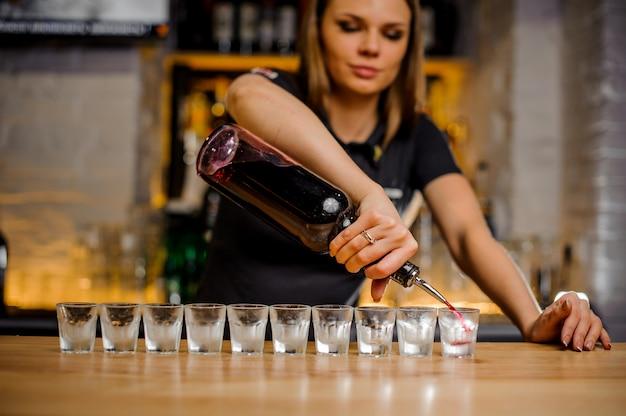 Bardame gießt alkohol in aufgereihte kristallstapel