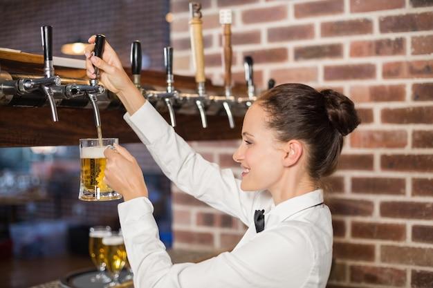 Bardame gießt bier ein