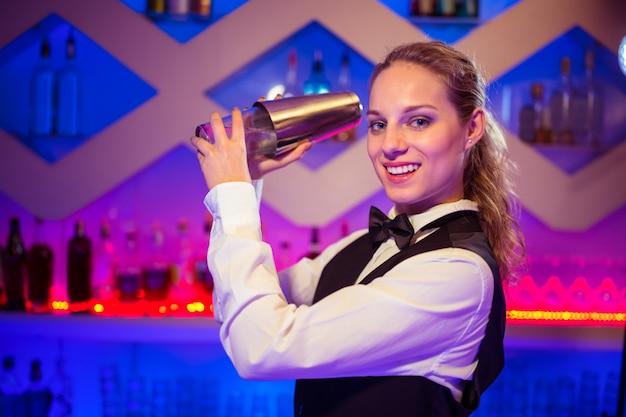Bardame mit cocktail-shaker an der theke