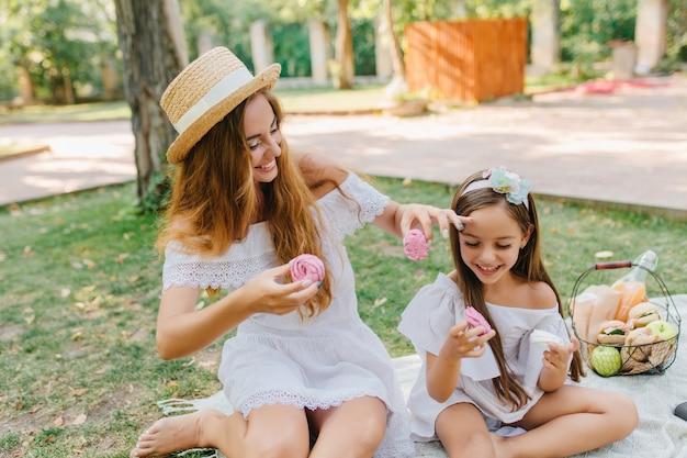 Barfüßige frau im hut mit weißem band, das auf decke nahe tochter sitzt und lächelnde kekse isst. außenporträt der glücklichen familie, die während des picknicks scherzt und herumalbert.