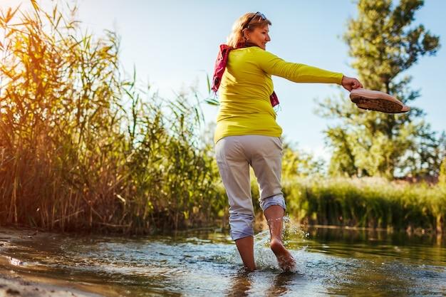 Barfüßige frau mittleren alters, die am frühlingstag am flussufer spaziert. ältere dame, die spaß im wald hat und die natur genießt.
