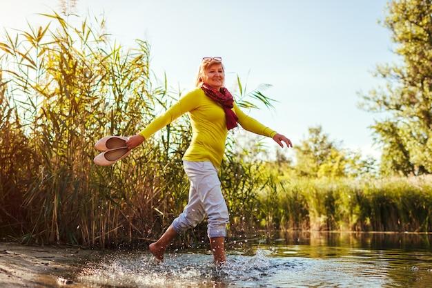 Barfüßige frau mittleren alters, die am herbsttag am flussufer spaziert. ältere dame, die spaß im wald hat und die natur genießt