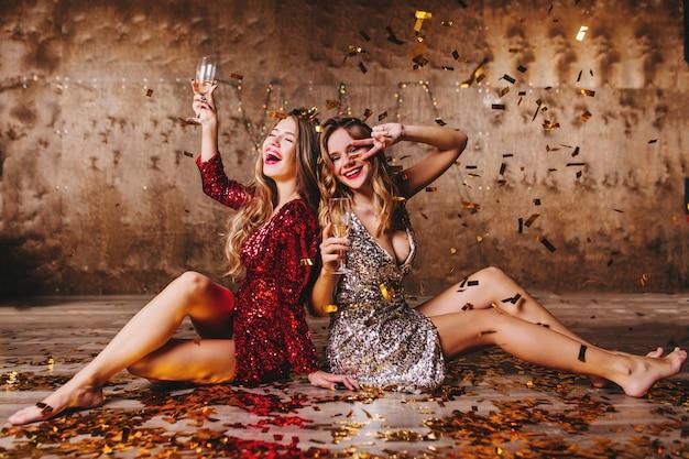 Barfüßige frauen trinken nach der party zusammen und sitzen auf dem mit konfetti bedeckten boden