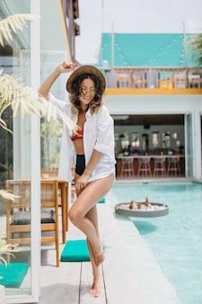 Barfuß dame im weißen hemd, das im sommerresort ruht. brünette frau trägt hut tanzen in der nähe von pool.